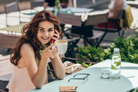 portrait of smiling woman with cup of coffee talking on smartphone in cafe