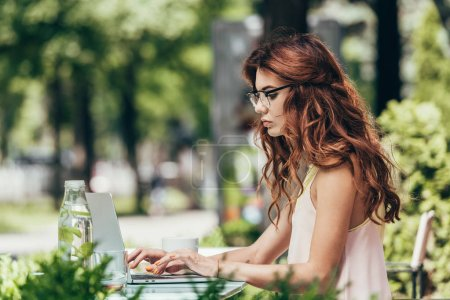 Photo for Side view of focused young blogger in eyeglasses working on laptop in cafe - Royalty Free Image