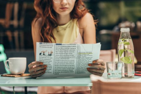 partial view of woman reading newspaper in cafe