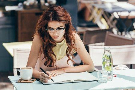 Photo pour Portrait de femme d'affaires en lunettes prenant des notes dans un carnet à table au restaurant - image libre de droit