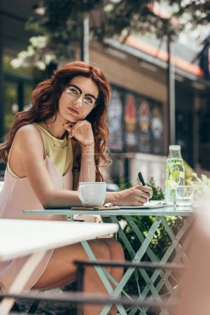 pensive businesswoman in eyeglasses sitting at table with notebook and cup of coffee in restaurant