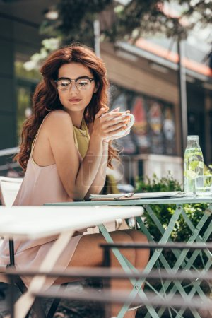 young businesswoman with cup of coffee sitting at table with notebook in restaurant