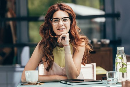 portrait of attractive businesswoman in eyeglasses sitting at table with cup of coffee and notebook in cafe