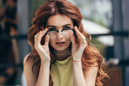 portrait of beautiful woman in eyeglasses looking at camera