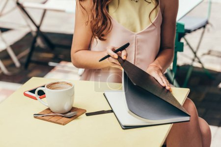 cropped shot of businesswoman with notebook at table in cafe