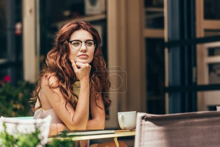 portrait of pensive businesswoman in eyeglasses at table with cup of coffee and notebook in cafe