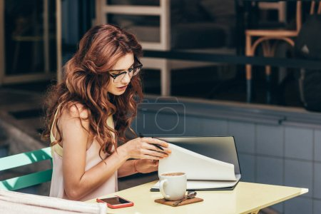 side view of young businesswoman in eyeglasses with notebook at table in cafe