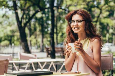 cheerful businesswoman in eyeglasses with cup of coffee sitting at table with notebook in cafe