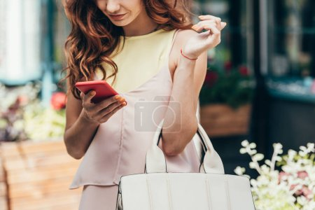 partial view of stylish woman using smartphone on street
