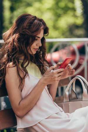 side view of young stylish woman using smartphone while resting on bench