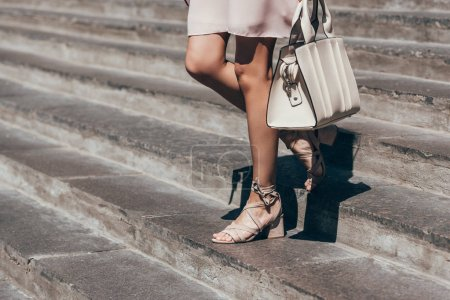 partial view of woman in stylish shoes walking down steps on street