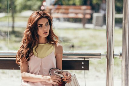 portrait of young pensive woman sitting on bus stop