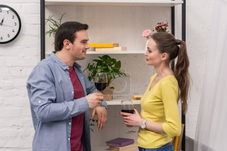 attractive adult couple with glasses of wine chatting in front of bookshelves
