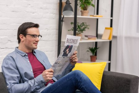 Photo for Handsome adult man reading newspaper while sitting on couch at home - Royalty Free Image