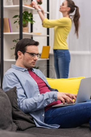 handsome adult man working with laptop while his wife looking for book on shelf blurred on background at home