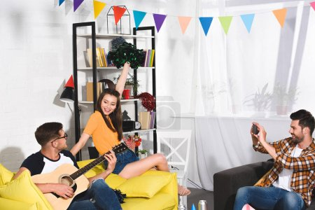 man with smartphone photographing friends playing guitar and singing at home party