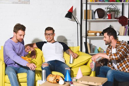 Photo for Handsome smiling young men drinking beer and eating snacks at home party - Royalty Free Image