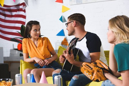 smiling young man playing guitar and looking at beautiful girl sitting on couch at home party