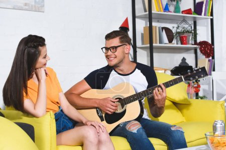 handsome smiling young man playing acoustic guitar and looking at beautiful girl sitting on sofa
