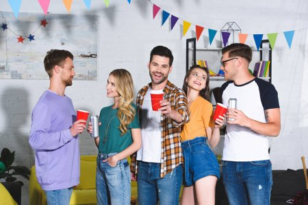 Photo for Happy young friends drinking beer while having fun together at home party - Royalty Free Image