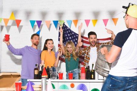 Foto de Recortar el tiro de hombre sosteniendo el barril de cerveza y mirando felizes amigos bebiendo bebidas alcohólicas en casa fiesta - Imagen libre de derechos