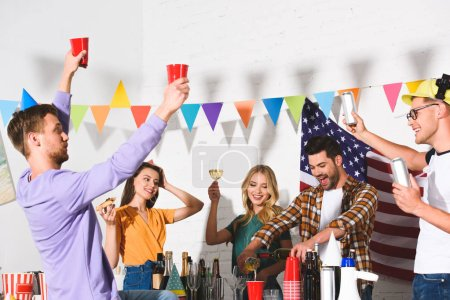 happy young friends drinking alcoholic beverages and having fun at home party