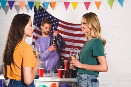 Foto de Hermosas mujeres jóvenes sosteniendo copas de vino y mirando el uno al otro mientras que hombre abrir botella de vino detrás de - Imagen libre de derechos