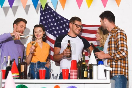 happy young friends drinking alcoholic beverages at home party