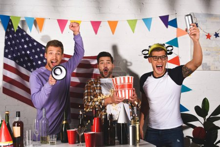 excited young men having fun and screaming at camera at home party