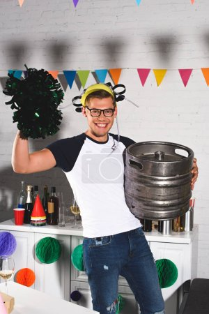 cheerful young man in beer hat holding pop-pom and beer barrel at home party