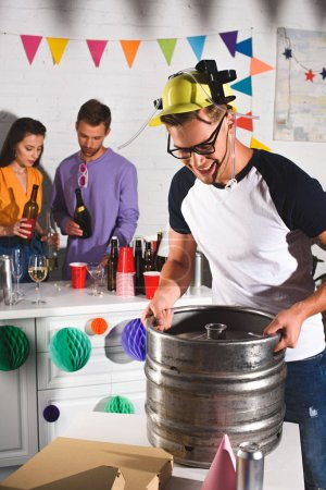 smiling young man holding beer barrel while friends drinking behind
