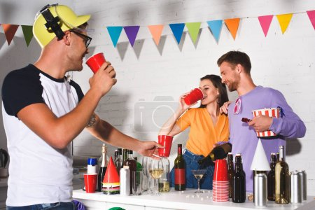 happy young friends drinking alcohol and partying together at home