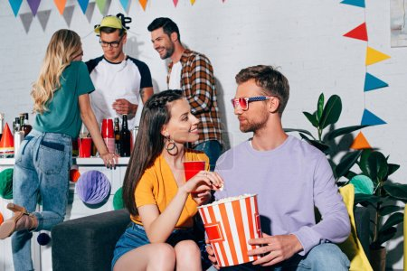 young man and woman looking at each other while drinking beer and eating popcorn at home party