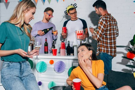 smiling female friends drinking alcoholic beverages and talking at home party
