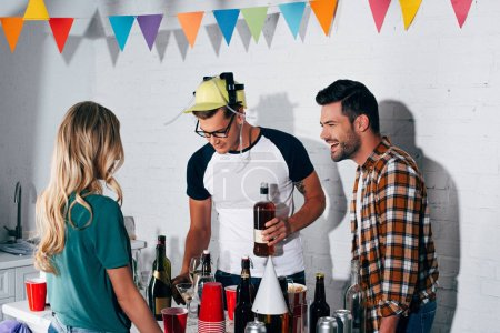 stylish smiling young people mixing alcoholic beverages at home party