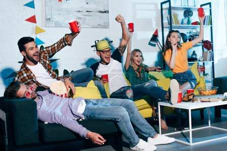 cheerful young people drinking beer and having fun at home party