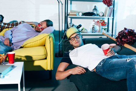 drunk young men sleeping on couches after home party