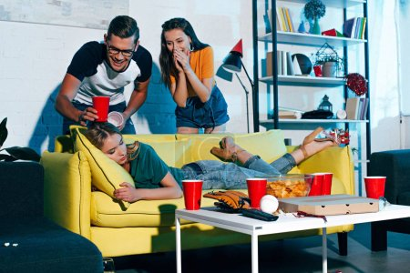laughing young people looking at drunk female friend sleeping on sofa after home party