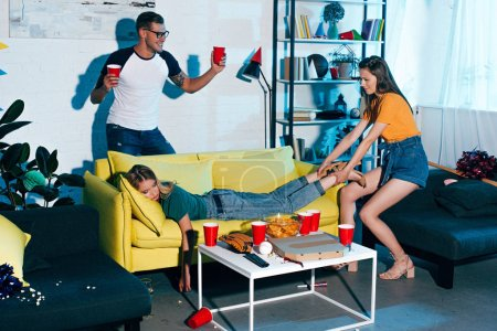 smiling man holding plastic cups and looking at girl pulling drunk female friend sleeping on sofa after home party