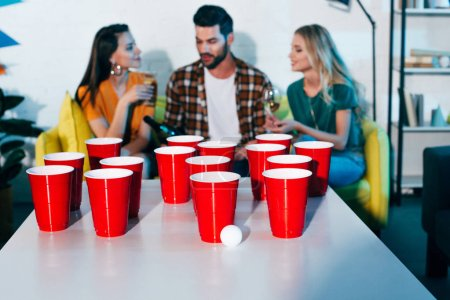 close-up view of plastic cups and ball for beer pong and young friend drinking wine behind