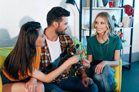 happy young people drinking wine and looking at each other while sitting on sofa at home party