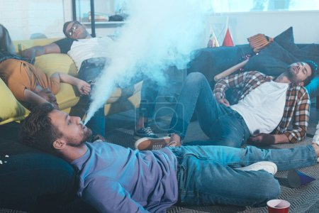 young man smoking electronic cigarette while drunk friends sleeping after party