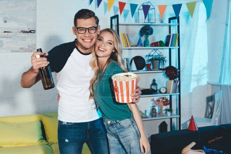 beautiful young couple with popcorn box and beer bottle smiling at camera and embracing at home party