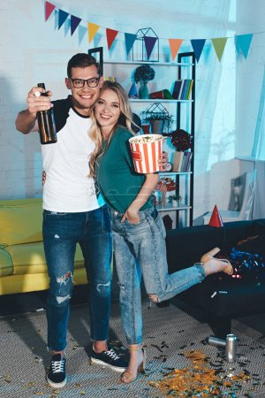 happy young couple with popcorn box and beer bottle smiling at camera and embracing at home party