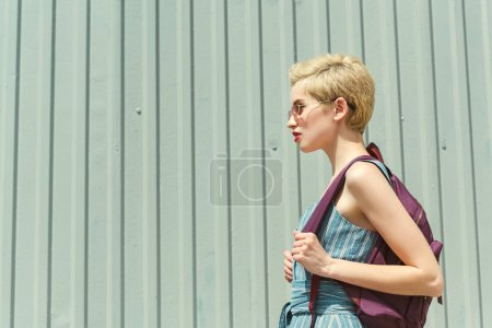 girl with short hair posing with backpack at wall