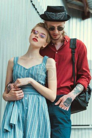 homme tatoué et superbe copine étreindre au mur