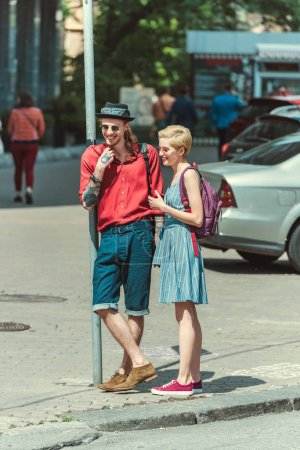 stylish couple of tourists with backpacks walking in city