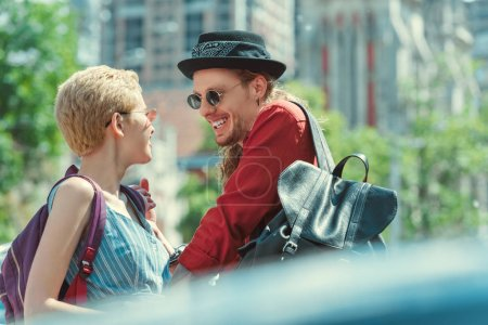 beautiful smiling couple with backpacks in city