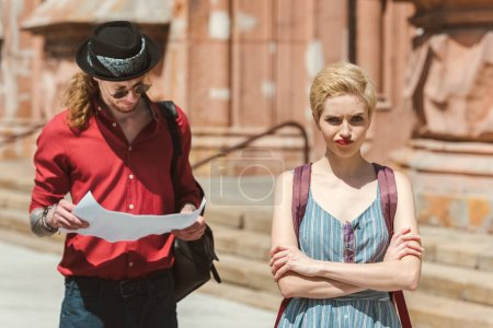 tourist looking at map while confused girlfriend with crossed arms standing near