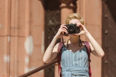 girl with short hair taking photo on camera